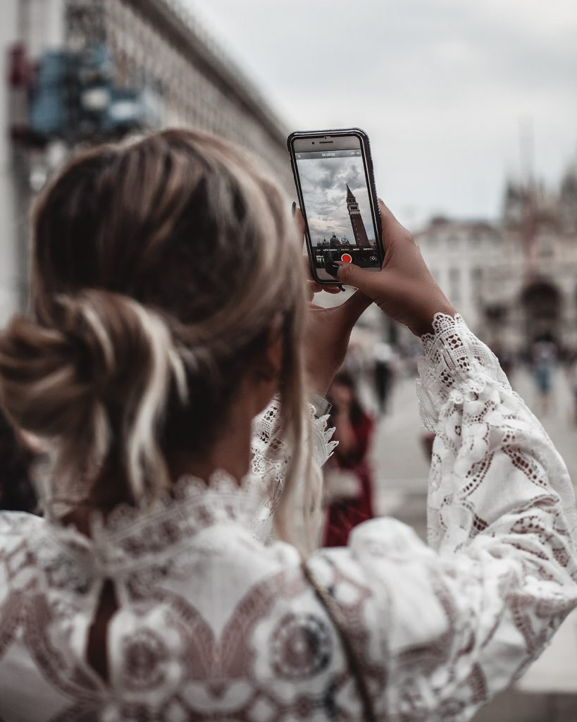 Trip to Venice woman wearing lace takes a photo with phone