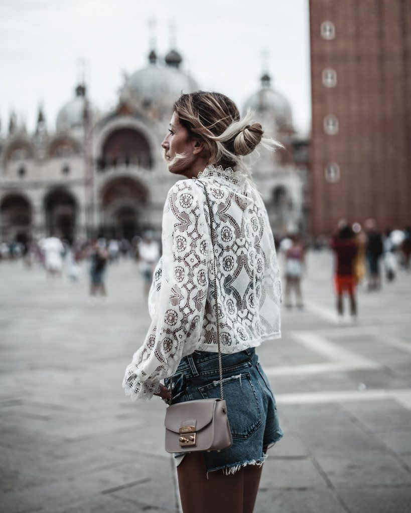 Trip to Venice wearing white lace top jeans shorts beige bag