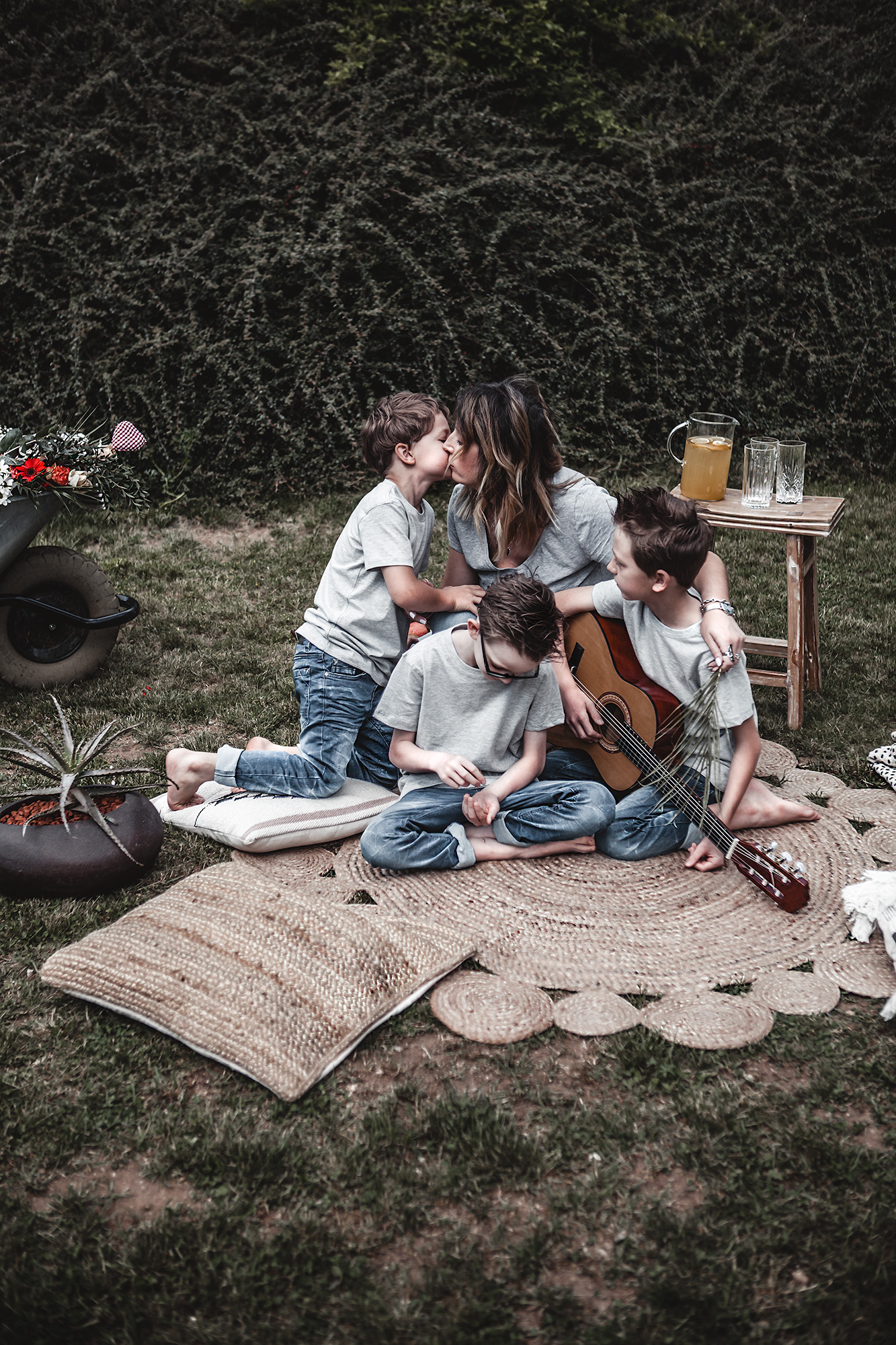 With these tips and decorative elements create a simple picnic decor in the garden and make the spot relaxing, familiar & inviting instantly. Family photo, mother and sons, picnic, garden, mother and kids, round jute rug. Mothers day photo.