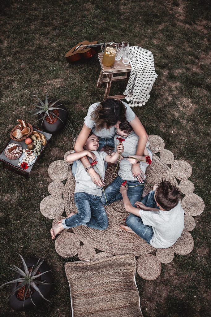 With these tips and decorative elements create a simple picnic decor in the garden and make the spot relaxing, familiar & inviting instantly. Family photo, mother and sons, picnic, garden, mother and kids, round jute rug.